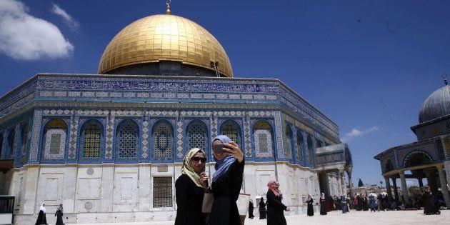 Deux palestiniennes se prennent en photo devant le Dome du rocher de la grande Mosquée Al Aqsa de