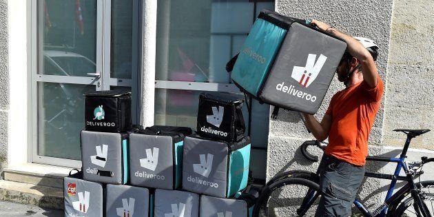 Un coursier de Deliveroo empile des sacs de livraison pour protester contre la modification de leur