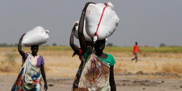 Des portent des sacs de nourriture à Nimini, au nord du Soudan du Sud ravagé par la guerre et la famine,...