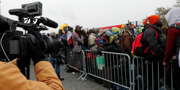 A TV cameraman films as migrants with their belongings queue at the start of their evacuation and transfer...