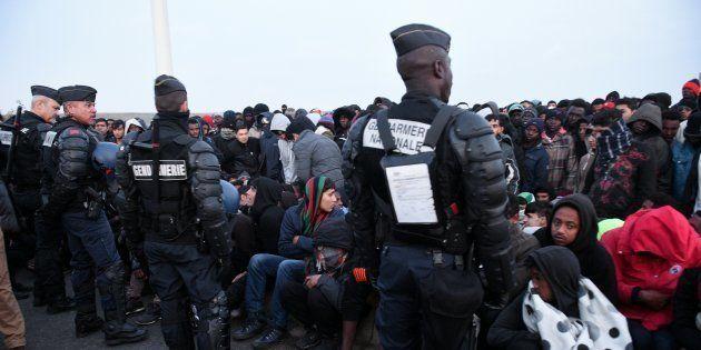 Des policiers surveillent la foule de migrants attendant d'être évacuée de