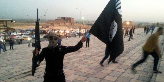 Un soldat de Daech brandit un drapeau de l'EI à Mossoul en Irak, en juin