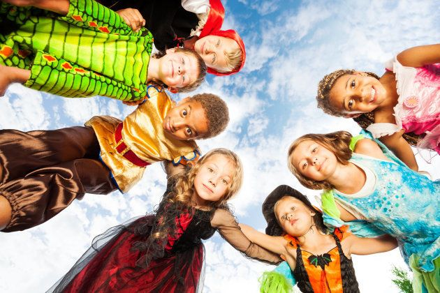 Happy group of children friends standing in circle in Halloween costumes outside and looking down
