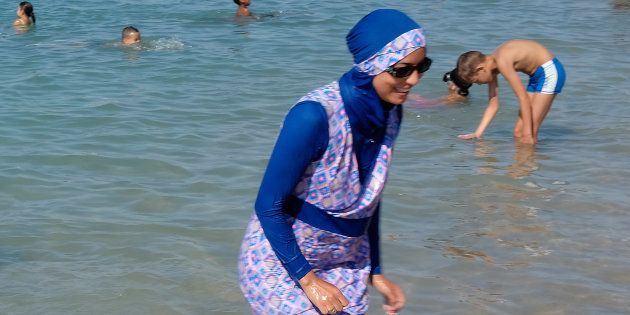 A woman wearing a burkini walks in the water August 27, 2016 on a beach in Marseille, France, the day...