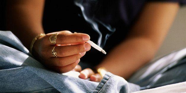 Un adolescent fume une cigarette