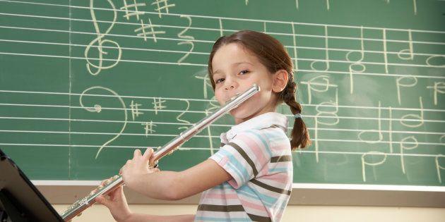 Schoolgirl (5-10) playing flute, smiling,