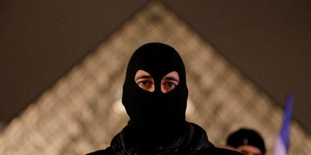 Un policier masqué devant la pyramide du Louvre lors d'une manifestation de policiers le 1er novembre...