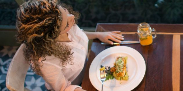 Lonely woman having dinner by herself at a
