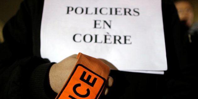 Un policier porte un écriteau lors d'une manifestation le 1er novembre à Paris. REUTERS/Christian