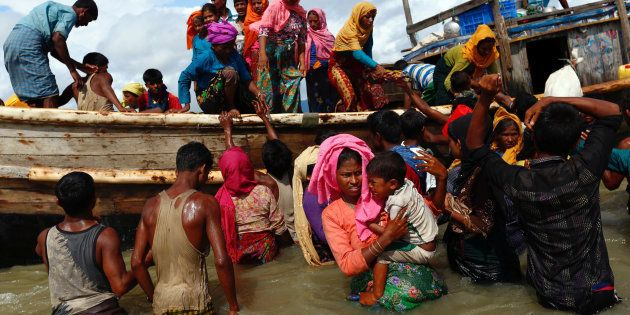 Rohingya refugees get off a boat after crossing the Bangladesh-Myanmar border through the Bay of Bengal,...