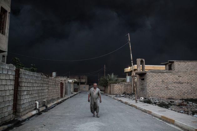 Un homme marche dans une rue de Mossoul. Derrière lui, un épais nuage de fumée provoqué par l'incendie...