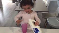 Cette fillette tente de se verser un verre de lait et c'est