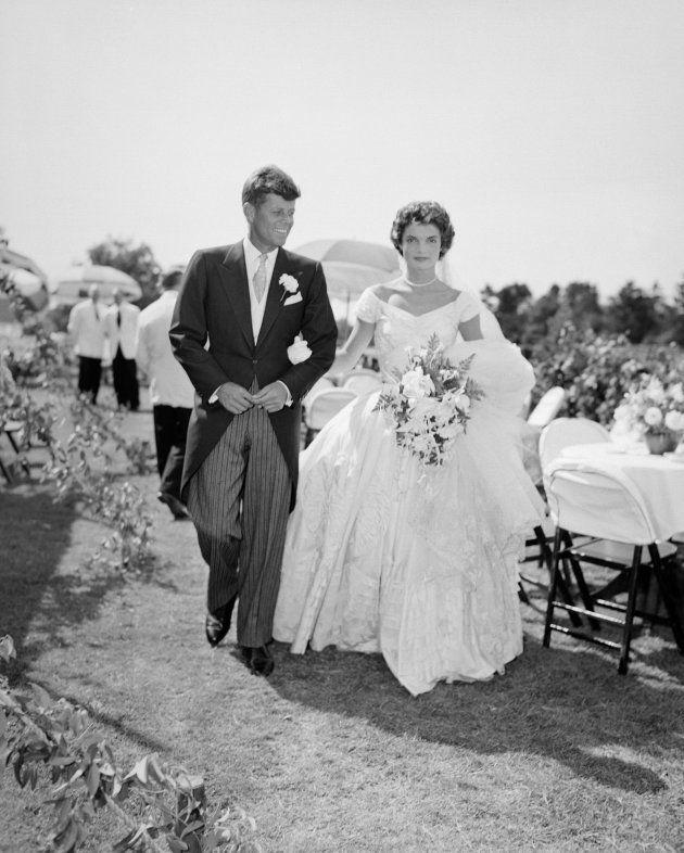A scene from the Kennedy-Bouvier wedding. Groom John walks alongside his bride Jacqueline at an outdoor...