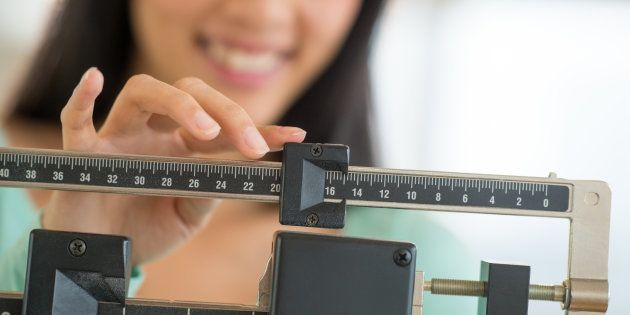 Midsection of mid adult Asian woman smiling while adjusting balance weight scale