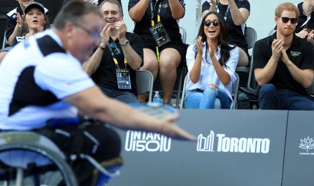 Prince Harry and Meghan Markle applaud as they watch Wheelchair Tennis at the 2017 Invictus Games in...