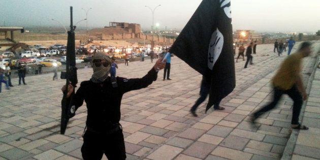 Un jihadiste du groupe État islamique porte le drapeau de l'organisation terroriste à Mossoul, en juin