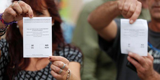 Des bulletins de vote du référendum en Catalogne brandis par des partisans du vote, samedi 30