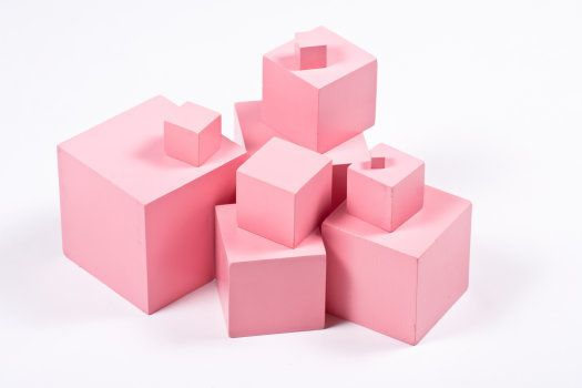 Montessori Pink Tower building blocks - sensorial material for elementary education. Isolated on white.