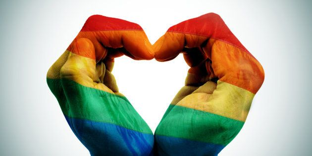 Mains jointes aux couleurs du drapeau LGBT