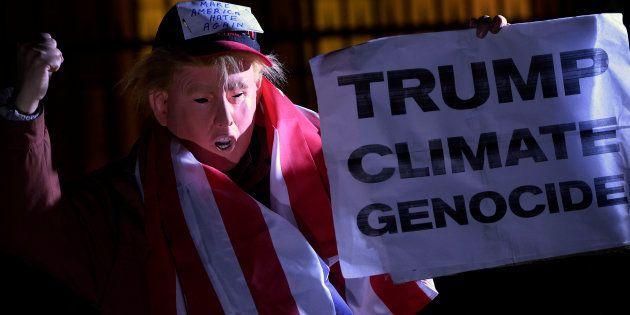 Un manifestant portant un masque représentant le Président Donald Trump proteste pour le climat devant...