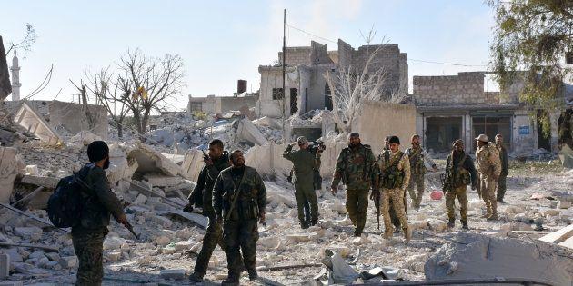 Les forces pro-gouvernementales syriennes inspectent des bâtiments pris aux rebelles dans les quartiers...