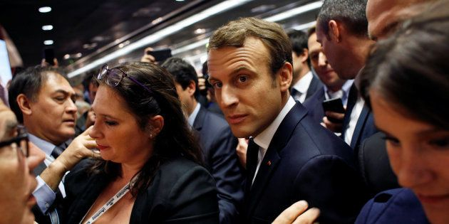 French President Emmanuel Macron (C) talks with people at a building trade congress in Paris, France,...
