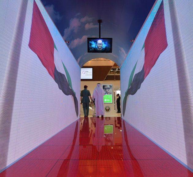 A policeman and visitor walk through a security tunnel at the Gitex 2017 exhibition at the Dubai World...