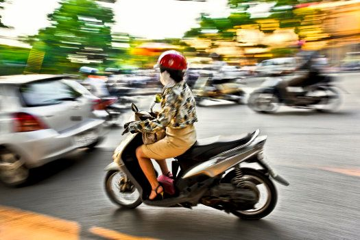 Young Woman with Anti-Pollution Mask Driving a Scooter, Hanoi, Vietnam