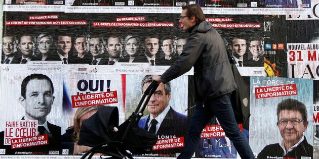 A pedestrian walks past campaign posters for the 2017 French presidential election, in Paris, France,...
