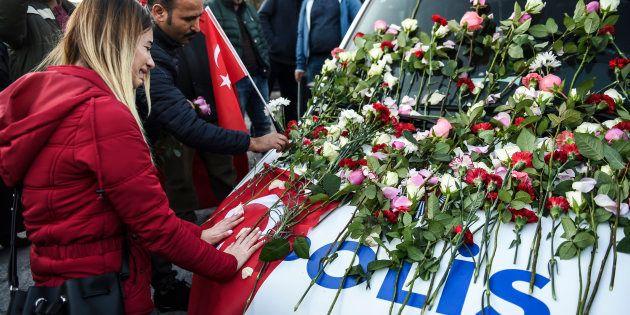 Une femme pleure devant un fourgon de police couvert de fleurs, lors d'un hommage aux victimes de l'attentat...