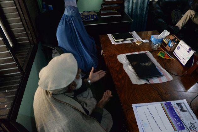Nadia, dans le cabinet de son avocat, assise aux côtés de son père, pour demander le divorce d'avec son...