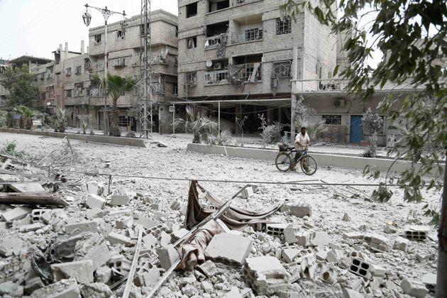 Un homme marche dans une rue détruite d'Hamouria, dans la région de la Ghouta en Syrie, en
