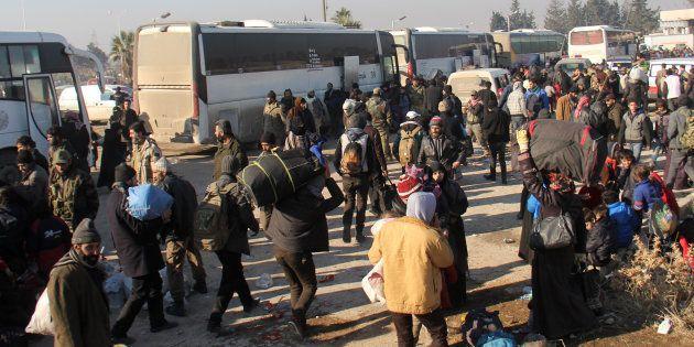 Des Syriens, évacués des quartiers rebelles d'Alep, arrivent le 19 décembre dans le quartier de Khan...