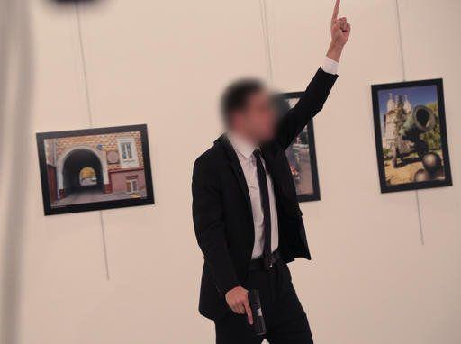 L'assaillant lève le bras au ciel après avoir tiré sur l'ambassadeur russe à Ankara, le 19