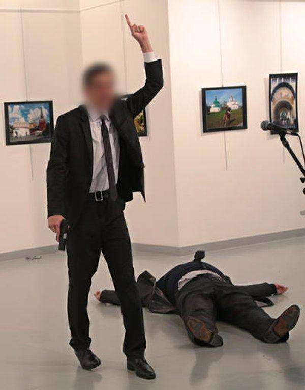Le tireur lève le bras au ciel près du corps de l'ambassadeur russe en