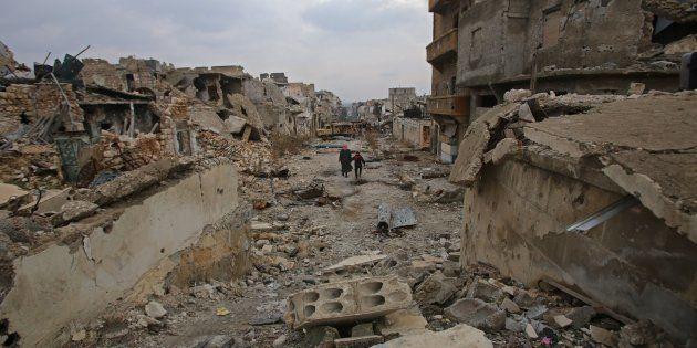 Des Syriens marchent à travers les ruines d'Alep dévastée, le 17 décembre