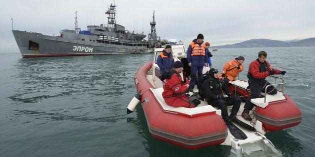 Des secouristes prennent part aux opérations de recherches sur le site du crash de l'avion militaire...