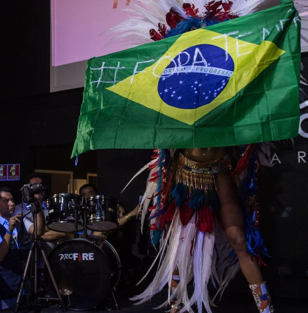 """Rosie Oliveira tenant le drapeau brésilien avec l'inscription """"Fora Temer"""""""
