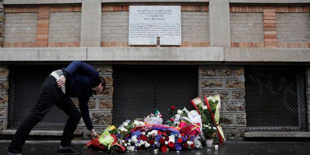 Un homme déposant des fleurs sous la plaque commémorative installée près du