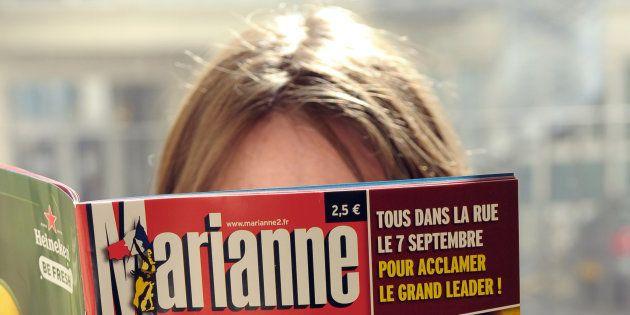 Une femme lit le magazine Marianne, aujourd'hui en cessation de paiement, en