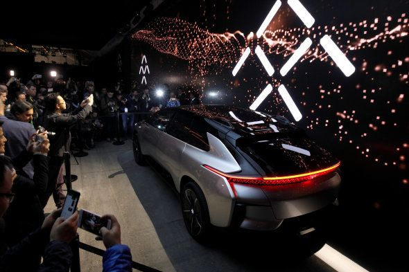 Journalists gather around a Faraday Future FF 91 electric car during an unveiling event at CES in Las...
