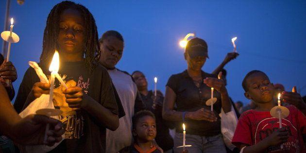 Des gens se rassemblent pour une veillée éclairée aux chandelles contre la violence armée dans le quartier...
