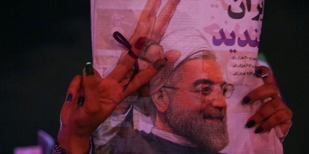 Un partisan du président iranien Hassan Rouhani tient son affiche en célébrant sa victoire lors des élections...