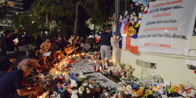 People place flowers and candles that were left in tribute at makeshift memorials to the victims of the...