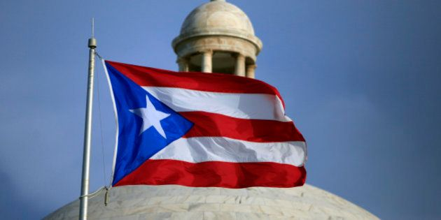 In this Wednesday, July 29, 2015 photo, the Puerto Rican flag flies in front of Puerto Rico's Capitol...