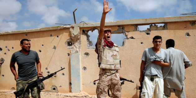 A member of Libyan forces allied with the U.N.-backed government gestures during a battle with Islamic...