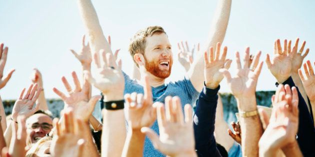 Smiling man standing with arms raised overhead in cheering crowd in stadium at sporting