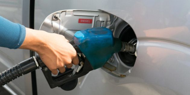 Men hold Fuel nozzle to add fuel in car at gas
