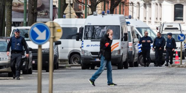 Police secure an area during a house search in the Etterbeek neighborhood in Brussels on Saturday April...