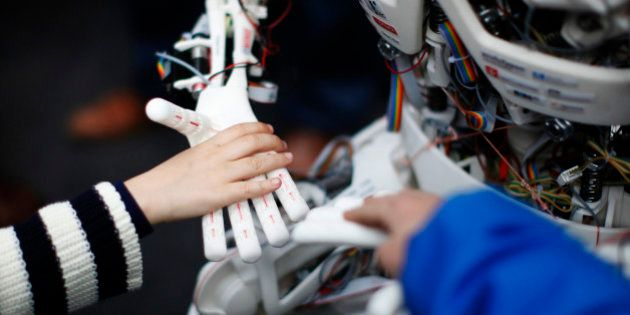 Children touch the hands of the humanoid robot Roboy at the exhibition Robots on Tour in Zurich, March...